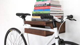 10 Ways to Solve Storage Problems in Small Spaces - Photo 2 of 10 - Finding a place to store larger items that are used daily is challenging. Thankfully, a beautifully crafted shelf like this from Knife and Saw elevates (both literally and figuratively) your commuter bike to the realm of sculptural art. It also provides room for your coffee table books.