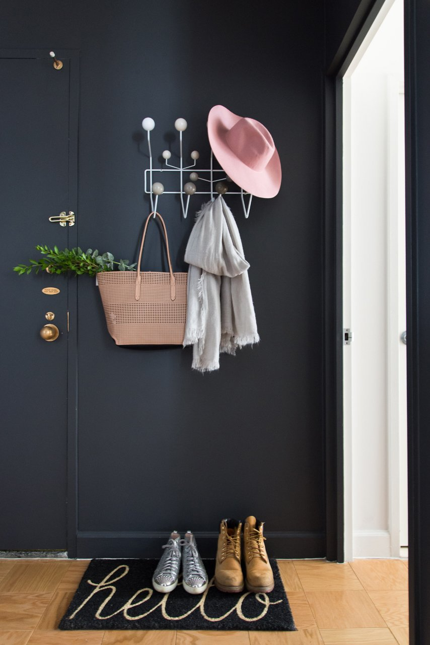 While black walls aren't the first thing you may consider for an inviting foyer, the dark walls are often in soothing contrast to the bright sunlight directly outside. The dramatic bold color also brings anything bright and colorful into stark relief.