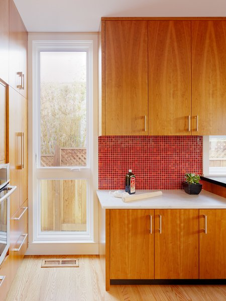 In this California home, a red mosaic tiled backsplash balances the lower white marble counter.