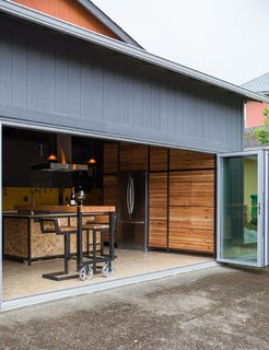 A 16 foot wide wall of folding glass doors welcomes you into the warm wood kitchen of this alley-fronting garage turned ADU.