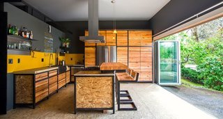 The kitchen features a moveable wood slab island on wheels that accommodates a variety of dinner guests in this 480 square foot space.