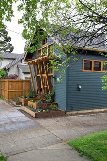A wood trellis offers coverage and marks the entry to this 700 square foot cottage ADU.