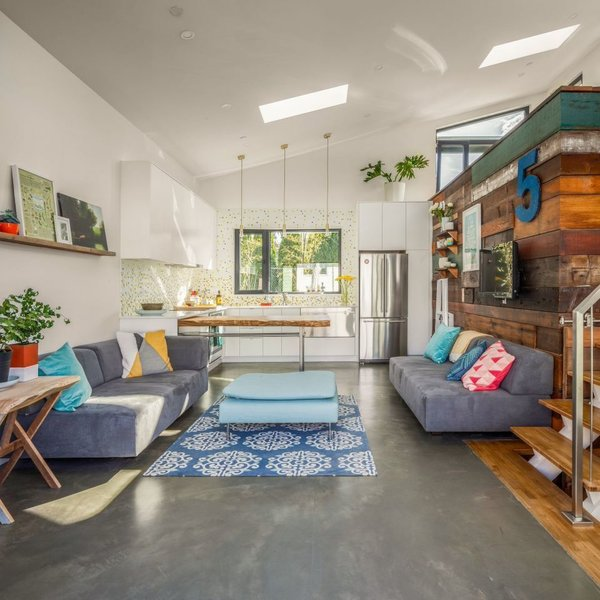 The interior of the space is filled with natural light thanks to the vaulted ceiling. The owner's work space resides in an upper loft, a volume highlighted by salvaged wood panels.