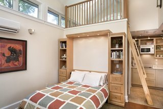 Built-ins, such as this Murphy Bed wall of storage, accommodate living in a small footprint. The ladder accesses a small loft above the bathroom for additional living space.