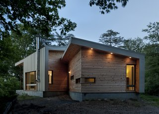 Discover 6 Amazing Riverside Homes - Photo 5 of 12 - Designed by GriD architects, this weekend retreat perched on a ridge overlooking the Potomac River optimizes both east-west exposure and views of the river. Its exterior cladding of wood and green-painted metal siding allude to the home's connection to its surroundings.