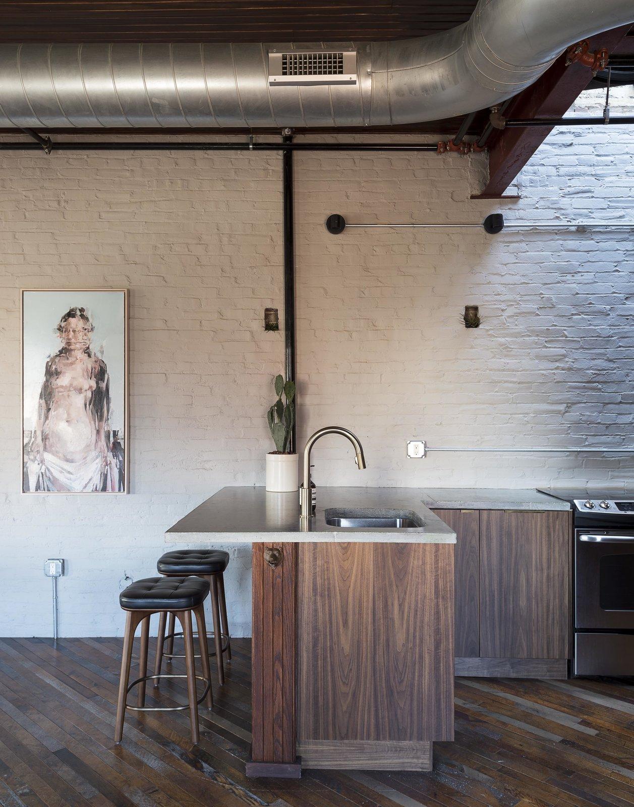 Tagged: Kitchen, Granite Counter, Medium Hardwood Floor, Wood Cabinet, Brick Backsplashe, Ceiling Lighting, and Track Lighting.  Mulherin's Hotel by Daniel Olsovsky