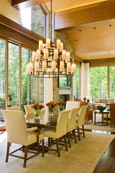Modern home with dining room, standard layout fireplace, pendant lighting, table, dark hardwood floor, and wood burning fireplace. Dining Room  Photo 3 of Ute Rock Residence
