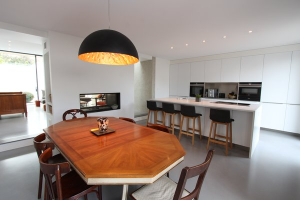 Modern home with kitchen, engineered quartz counter, white cabinet, concrete floor, pendant lighting, metal backsplashe, cooktops, wall oven, ceiling lighting, undermount sink, and microwave. Photo 10 of Extension of a house in Geneva