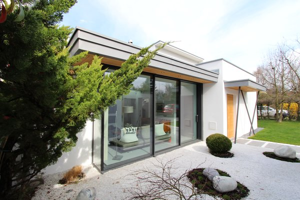 Modern home with outdoor, boulders, small patio, porch, deck, and front yard. The existing courtyard was transformed into the living room Photo 12 of Extension of a house in Geneva