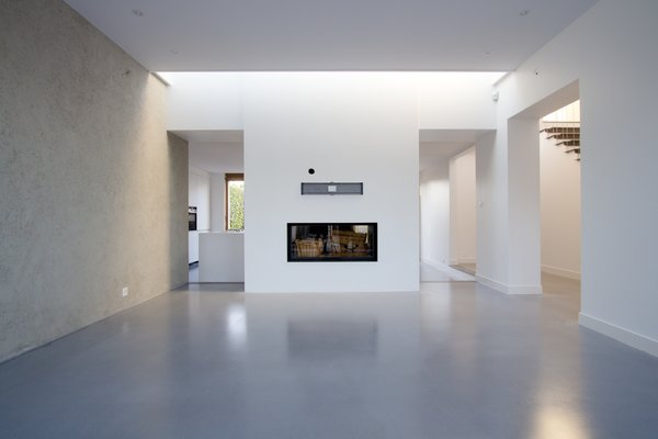 Modern home with living room, two-sided fireplace, and wood burning fireplace. Photo  of Extension of a house in Geneva
