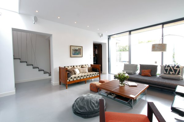 Modern home with living room, recessed lighting, sofa, chair, coffee tables, and concrete floor. Photo 3 of Extension of a house in Geneva