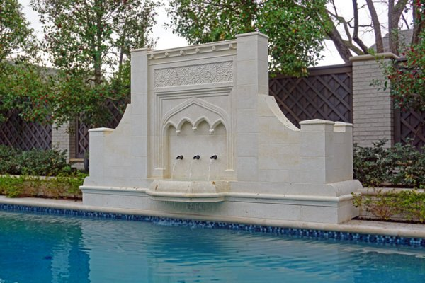 Modern home with outdoor, trees, back yard, wood fence, large pool, shrubs, and stone patio, porch, deck. Fountain Design by Tim Alexander  Photo  of Custom Gothic Pool Fountain