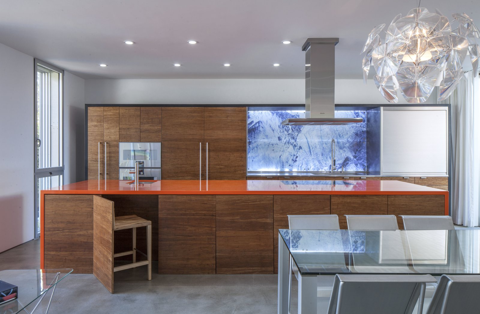 "The design and use of color is inspired by dramatic Icelandic landscape to create contrasting stimulating interiors. The orange (volcanic) creates a multi-functional gathering point in the heart of the house. The swimming pool has a blue lagoon color and the cabinets are the colors of glaciers and lava. To maximize the use of space, the ""disappearing"" kitchen chairs are easily stored under the island"