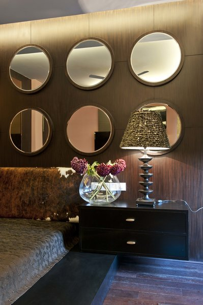 The set of mirrors on the wall above the bed balances the warm tone of other elements of this bedroom. Photo 4 of In the details modern home