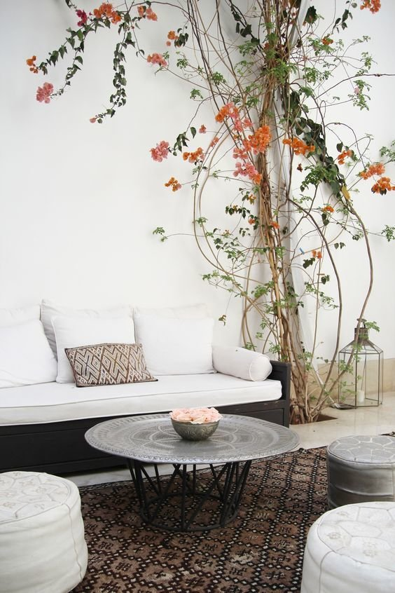 Moroccan rugs, leather poufs and hand hammered silver tables make stark spaces comfortable.  Photo 7 of 10 in 10 Ways to Use Rugs in Your Outdoor Space This Spring