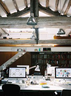 This multi-level attic is home to a creative firm that use the lower space for its production studio and the upper space for meetings or traditional work.