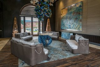 """16' 6"""" ceilings allowed for oversized chandeliers to be used in community spaces; Mexican and modern design are expertly juxtaposed through wood and hand-blown glass."""