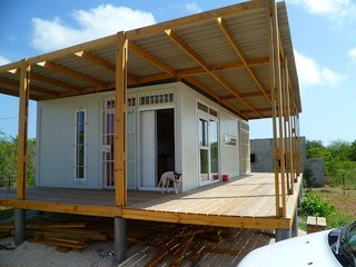 10 Beautiful Island-Style Shipping Container Homes - Photo 3 of 11 - Bonaire, a former Netherlands Antilles territory and now a special municipality directly under the Netherlands, hosts this container property on 1,260 square meters of land. The property is has off-grid electricity via four solar panels on the roof.