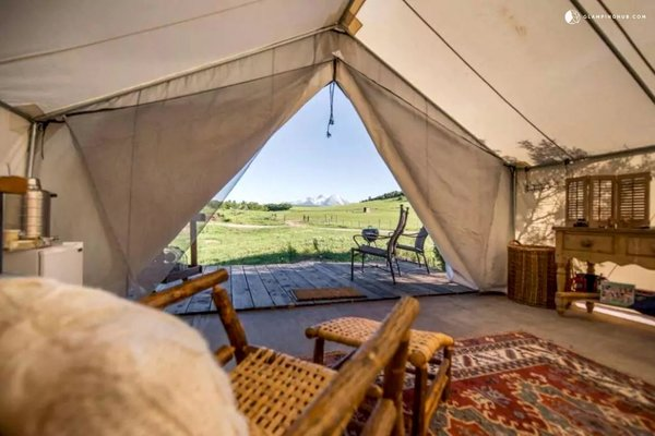 12 Terrifically Glamorous Camping Options - Photo 2 of 13 - This unique safari tent can be found near White River National Forest, Colorado, and is perfect for a glamping getaway. The tent features a beautiful California king four-poster bed that guarantees a peaceful sleep. There is also a deck where guests can enjoy soaking in the beautiful views.