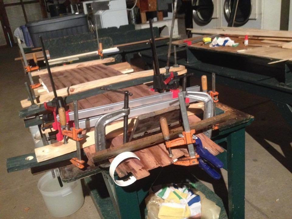 Clamping the deck and bottom to the skeleton by all means necessary—threaded rods, G-clamps, strips of PVC pipe and later, those water bins on top.  Photo 10 of 26 in Crafting a Hollow Wood Surfboard from Old-Growth Redwood