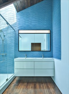 These 10 Designers Are Experts at Creating Colorful Bathrooms That Pop - Photo 5 of 11 - Blue tiles reflect daylight on the dark wooden floors and ceiling frame. Martin Fenlon Architecture is a Los Angeles-based firm that's committed to seeking sustainable architecture in innovative spaces.