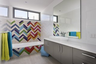 These 10 Designers Are Experts at Creating Colorful Bathrooms That Pop - Photo 6 of 11 - No need to stick to a single color; a bold, multi-hued mosaic effect here, combined with the primary colored towels makes the difference. Exactus was established by Ralph Brewer, a builder with over 25 years experience in the industry.