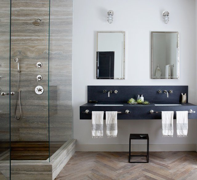 New York City–based designer Jenny Wolf  used mirrors and patterns for this windowless bathroom. Tall mirrored medicine cabinets and a glass shower amplify light from the interior fixtures, brightening up the space. Wolf used built-in cabinets to save floor space. A herringbone wood floor gives the illusion of a larger and warmer bath. These 10 Designers Are Experts at Creating Colorful Bathrooms That Pop - Photo 11 of 11