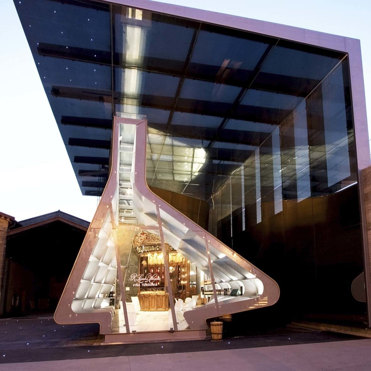 "López de Heredia commissioned Hadid to crate a new extension to their existing bodegas, which now houses the old stand and a shop, entertainment and exhibition area, citing  Photo 4 of 18 in ""Queen of the Curve"": 18 Influential Works by Zaha Hadid"