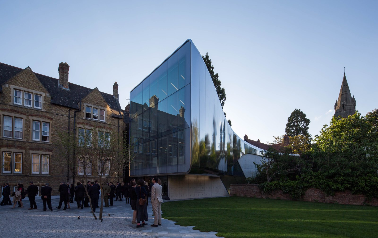 """The Investcorp Building integrates new academic and research facilities within a design defined by the existing built and natural environment of the college. The project maintains the detached character of the college's current buildings, allowing them to be read as separate elements, while introducing a contemporary building that conveys the past, present and future evolution of the college, university and city. Tagged: Exterior and Glass Siding Material.  Photo 16 of 18 in """"Queen of the Curve"""": 18 Influential Works by Zaha Hadid"""
