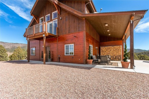 This off-the-grid mountain barn home located in the heart of the Rockies sits at 7,500 feet and has expansive views of the foothills below. The model is a Barn Pros 36 ft. x 36 ft. Denali barn apartment with a partially-enclosed shed roof on one side for outdoor seating and an entertainment area.