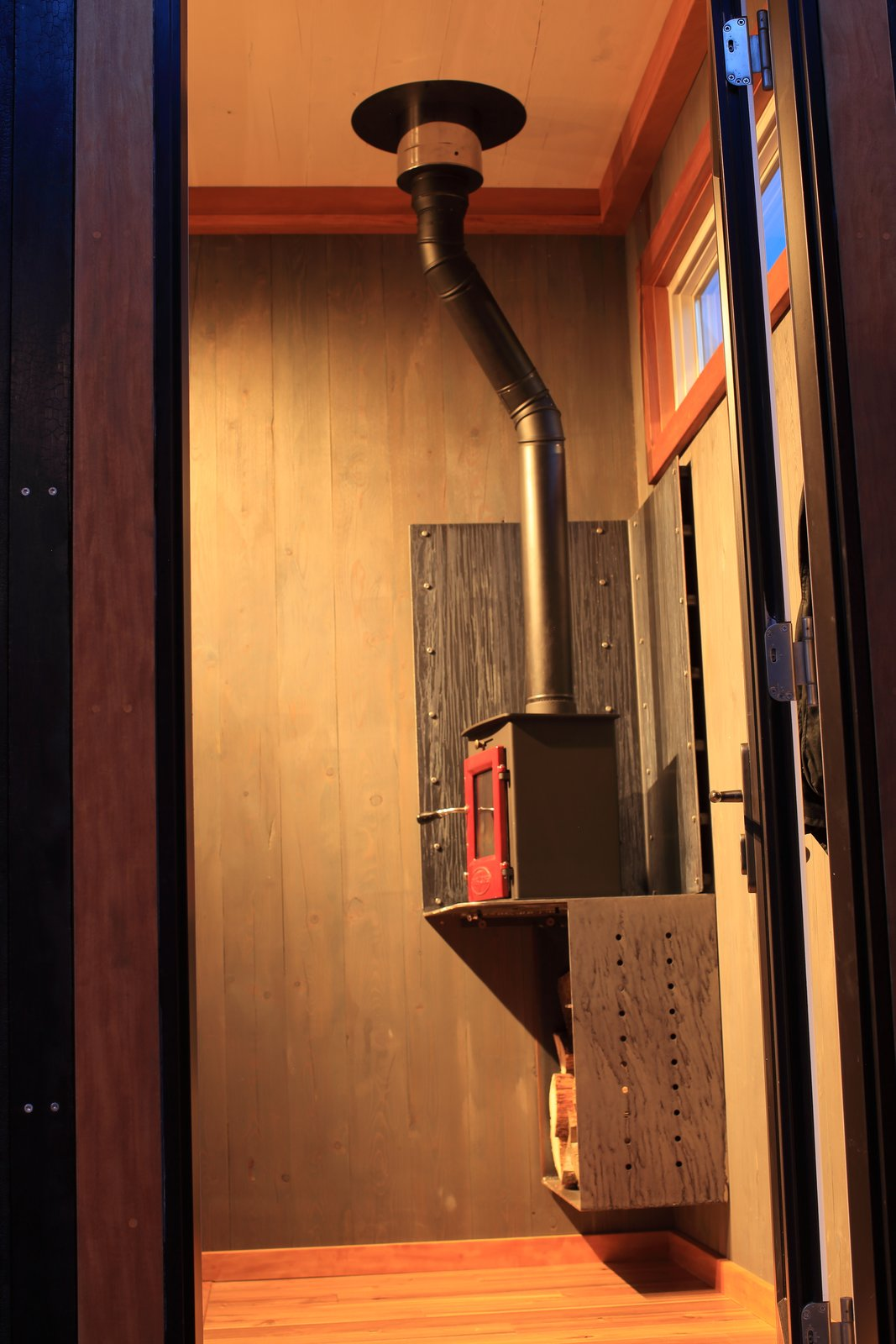 The Dwarf wood-burning stove by Utah's Tiny Wood Stoves won't overheat the small space. Because the solid cross-laminated-timber walls have the same structural strength throughout, the custom steel stand and wood box can hang directly off the wall. Tagged: Living Room, Wood Burning Fireplace, Track Lighting, and Ceiling Lighting. The Adirondack by Cubist Engineering