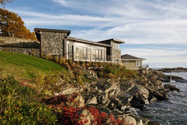 Modern home with outdoor, stone patio, porch, deck, boulders, and back yard. The Lighthouse, ocean side, with the adjacent cottage in the background. Photo  of The Lighthouse