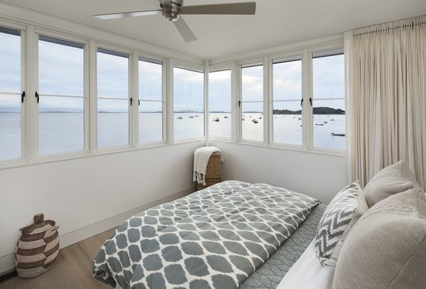 Modern home with bedroom, bed, and light hardwood floor. The view from the tower bedroom, Boston in the distance. Photo 5 of The Lighthouse