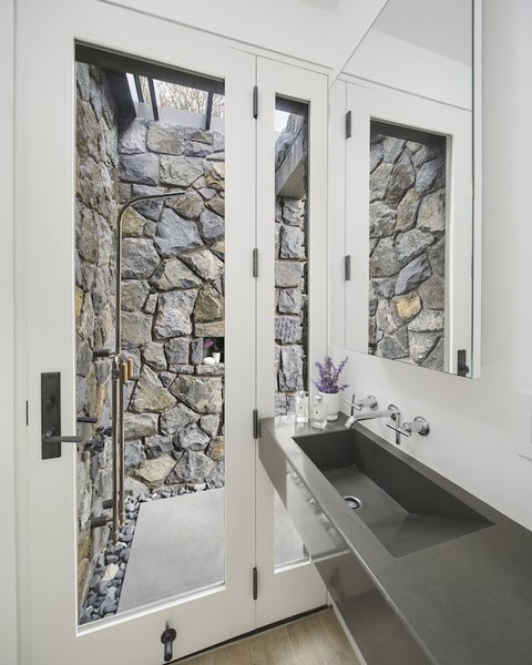 Modern home with bath room, concrete counter, medium hardwood floor, concrete floor, wall mount sink, open shower, and stone slab wall. A stone wrapped outdoor shower in the second bath. Photo 8 of The Lighthouse