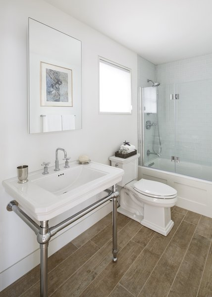 Modern home with bath room, porcelain tile floor, pedestal sink, enclosed shower, alcove tub, and two piece toilet. Clean and simple bathroom. Photo 7 of The Lighthouse