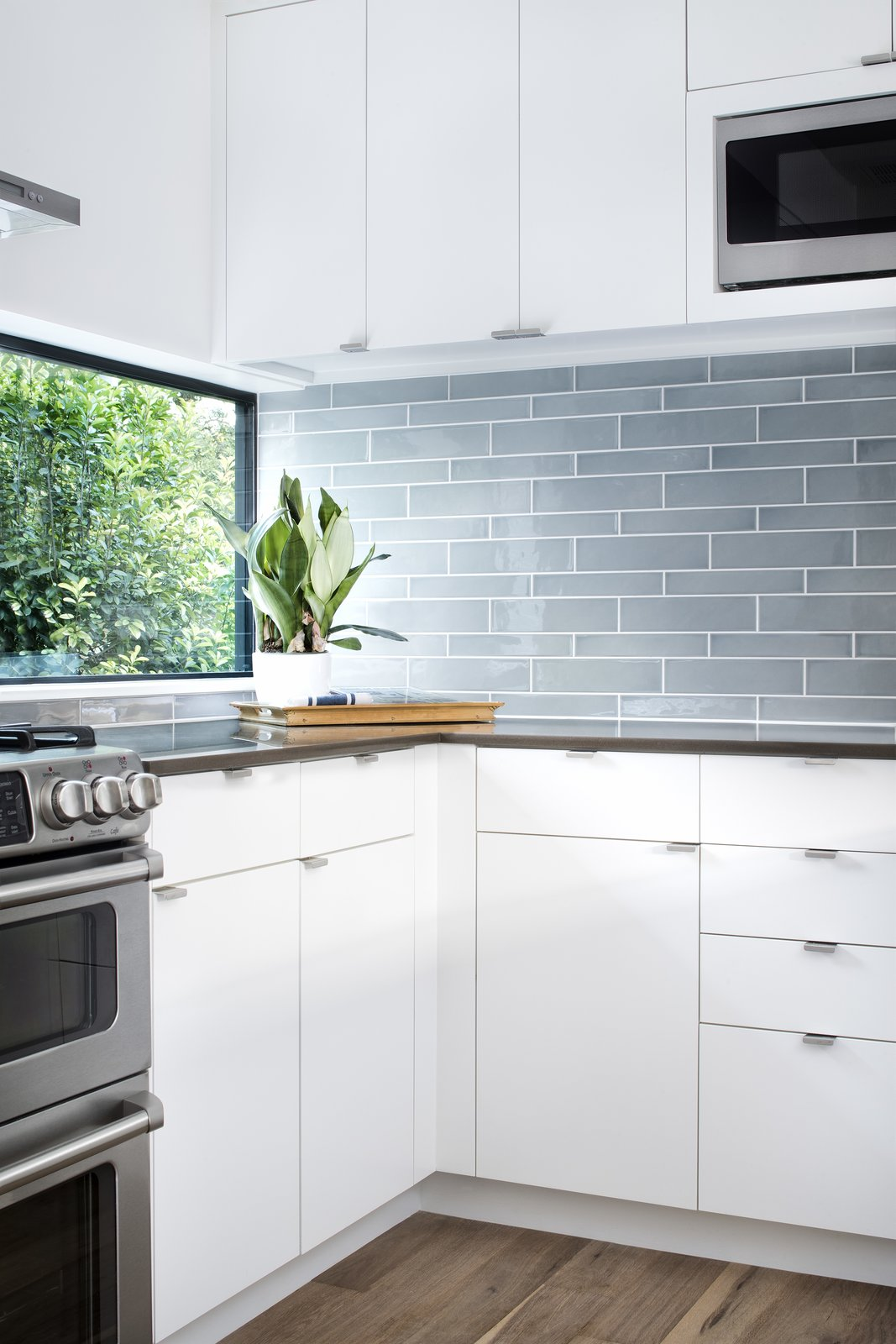 A large horizontal windows in the kitchen washes natural light across the blue accent tiles.  www.clarkrichardson.com