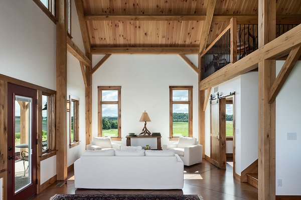 The living room showcases the use of clean, simple lines, letting the hand-crafted timber frame and the view out the windows do all the talking.  Photo  of Timber Frame Barn Home in a Hayfield modern home
