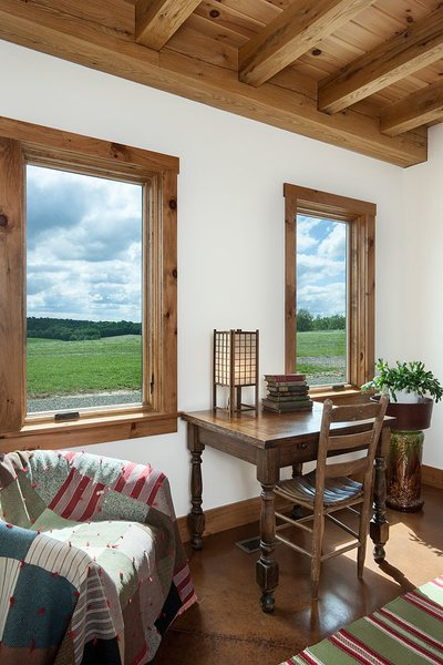 The office space off the living room also doubles as a guest room. Photo 5 of Timber Frame Barn Home in a Hayfield modern home