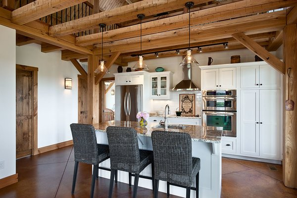 The kitchen, accented by rough-hewn timbers overhead. Photo 8 of Timber Frame Barn Home in a Hayfield modern home