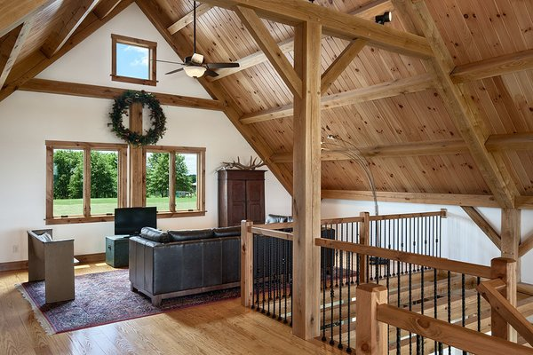 This side of the loft often serves as movie room.  Photo 10 of Timber Frame Barn Home in a Hayfield modern home