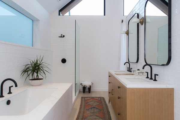 Modern home with bath room, enclosed shower, undermount sink, marble counter, soaking tub, corner shower, and subway tile wall. Photo 5 of Love Street Residence