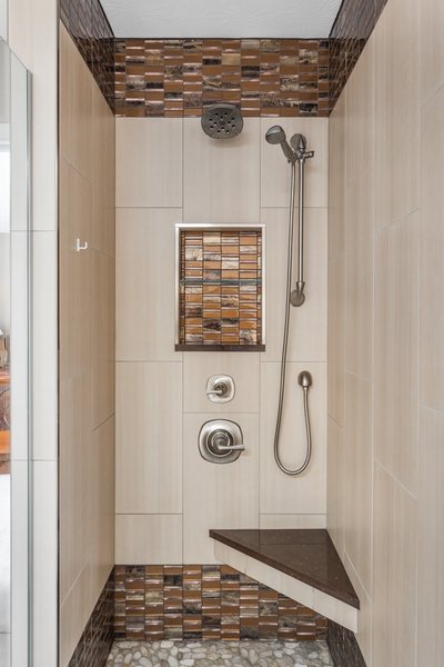 This enlarged shower includes a seat for comfort and two sources of water for an enhanced shower experience. The mixture of tile creates an elegant feel to the space. Two recessed niches provide ample storage for soaps, shampoos, and other bathing essentials. Note the wall tile is the same used on the bathroom floor. Photo 3 of Bathroom Remodel for 1980s Indianapolis Home modern home
