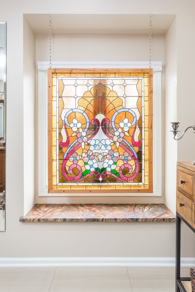 We added a window seat using the same marble as the vanity. A lovely stained glass piece provides privacy and ties in the colors found in the marble and the bedroom decor. Photo 4 of Bathroom Remodel for 1980s Indianapolis Home modern home