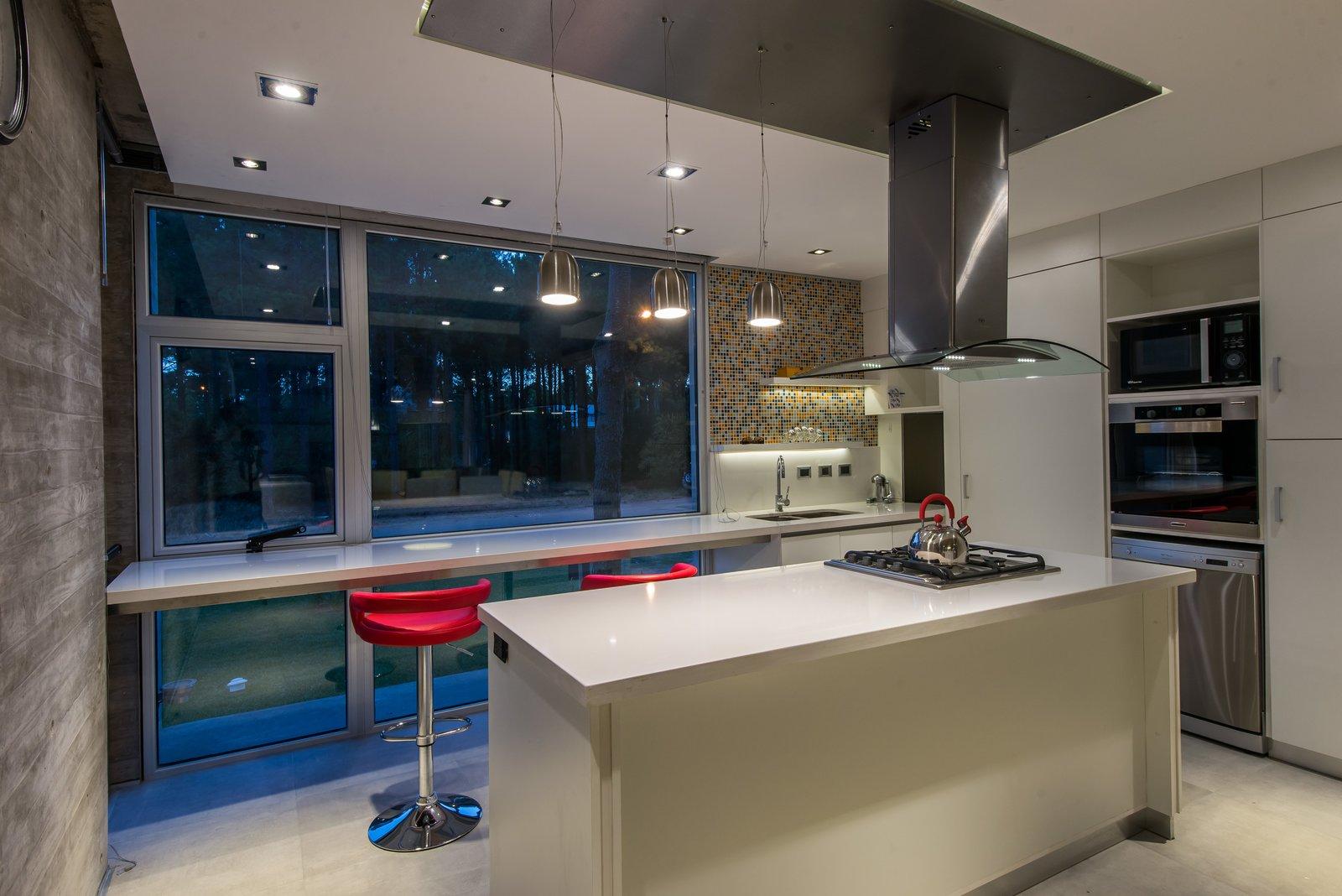 Tagged: Kitchen, Quartzite Counter, White Cabinet, Porcelain Tile Floor, Mosaic Tile Backsplashe, Wall Oven, Ceiling Lighting, Refrigerator, Cooktops, Drop In Sink, Microwave, and Dishwasher.  Casa Batin by Estudio Galera