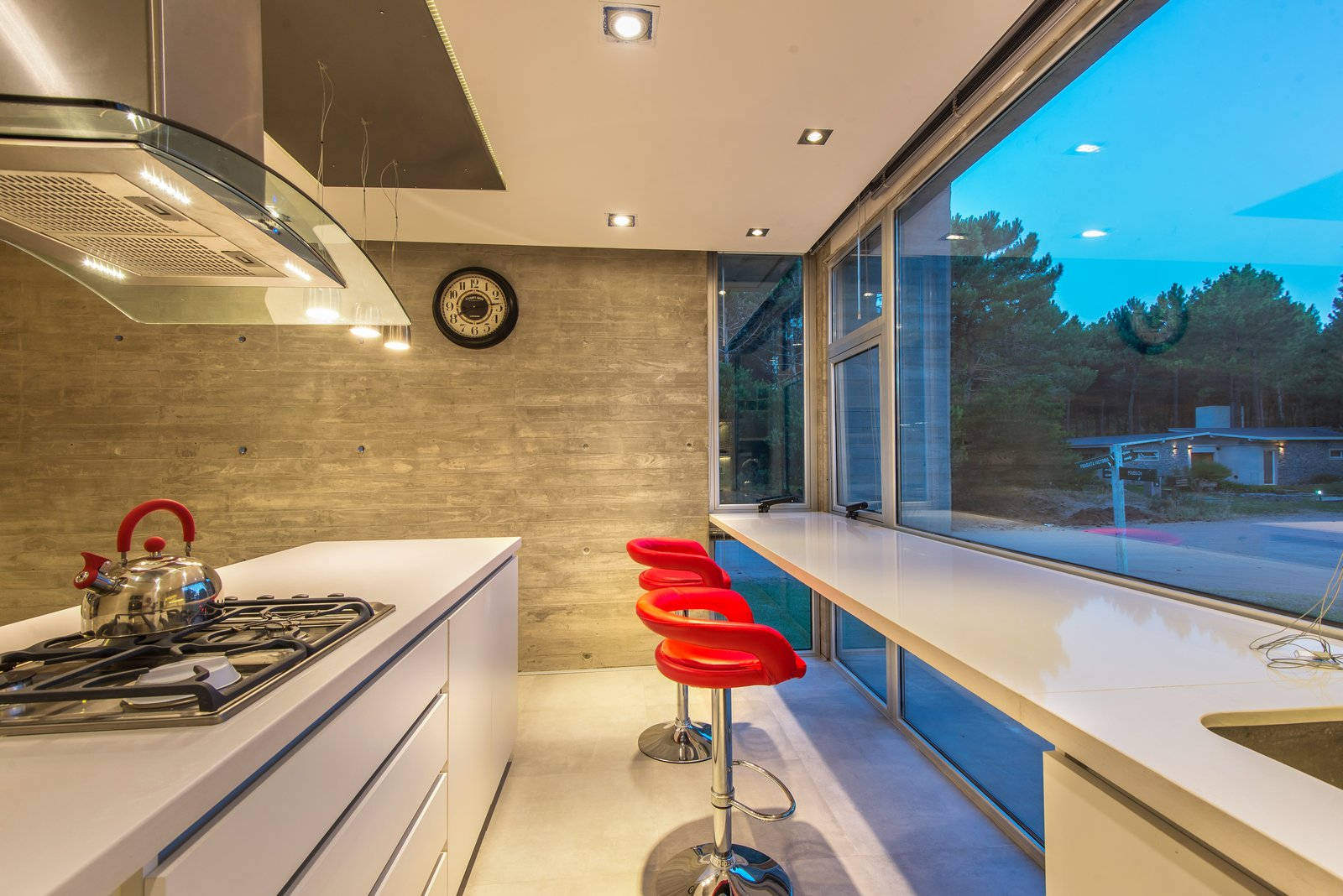 Tagged: Kitchen, White Cabinet, Concrete Backsplashe, Quartzite Counter, Porcelain Tile Floor, Cooktops, Ceiling Lighting, and Drop In Sink.  Casa Batin by Estudio Galera