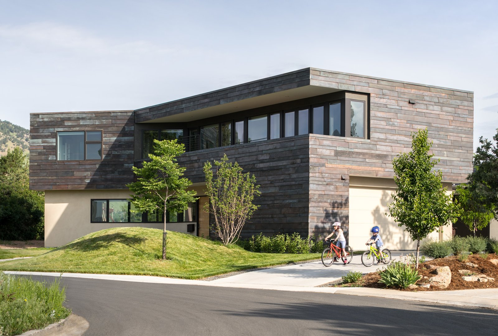 The restrained exterior material palette (copper siding, stucco, and bronze metal clad accents) accentuates the bold forms and angles.
