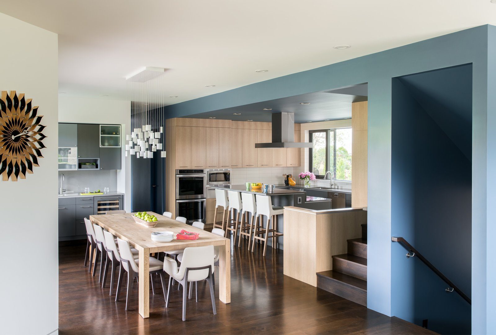 The interior palette echoes the simple use of materials with walnut floors, oak and grey cabinets. Restraint is contrasted with whimsy, however with unexpected pops of bold color throughout the home: a blue ceiling and walls wrap around the kitchen and centrally located stair articulating the service side of the home.  Sunset House by HMHAI