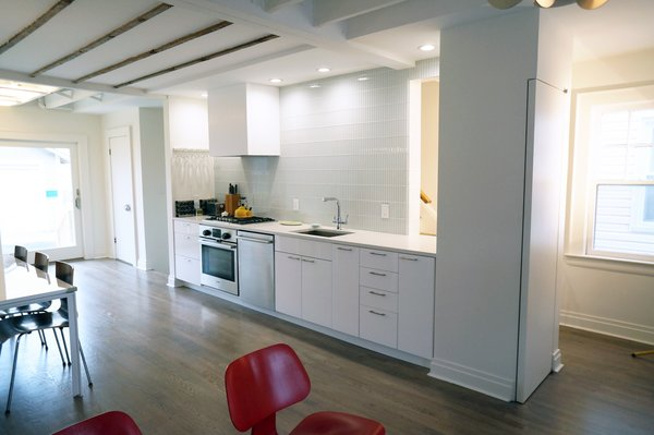 White Box – Kitchen and Living spaces  We were asked by our client to remove two walls in order to open the small space that measures 17' wide by 31' long. Two simple ideas drove the design; Light and duality of space. Guided by both we started with what we believe is critical to every project – process of discovery. The proposed design uses white and dominating color for walls, cabinets and the built in bench. Light colored wood floor will add to the light appearance of space shell. As all dividing walls were removed, perimeter walls were charged with functions; linear kitchen, bench next to dining table, and pantry closet. Avoiding upper cabinets allow the design to be open and make use of the wall as a dynamic element –otherwise a monochromatic space. The newly created functional void connects both ends of space and creates what appears to be a larger and brighter spatial experience. Photo  of NY Metro modern home