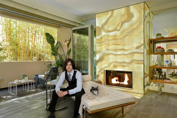 Chad Rogers and his Chihuahua Starla in front of a custom vanilla Onyx fireplace in the living room of his newly renovated Beverly Hills condo. Photo  of Rogers Residence modern home