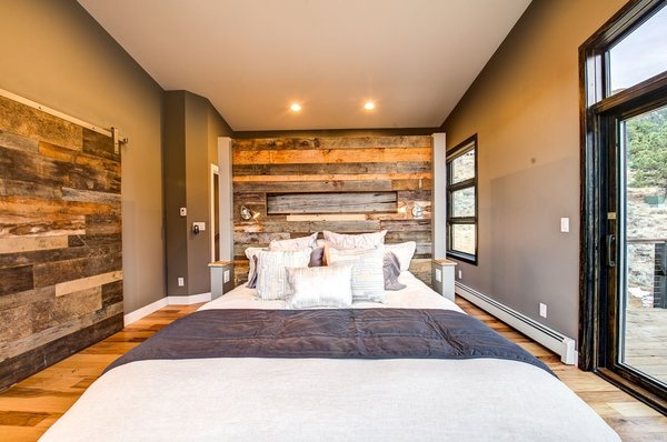 The master bedroom makes copious use of reclaimed barn wood.  Photo 20 of Ascent Estes Park modern home